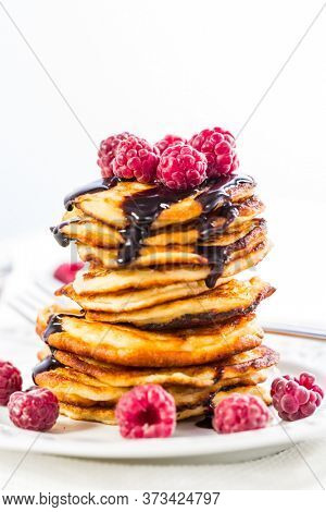Delicious cottage cheese pancakes with fresh raspberry and chocolate sirup. Curd fritters.