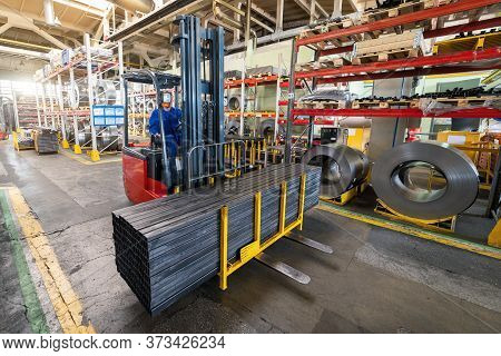 A Forklift Carries A Pack Of Metal Profiles. Plant For Processing Metal Profiles And Wire.