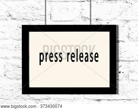 Black Wooden Frame With Inscription Press Release Hanging On White Brick Wall