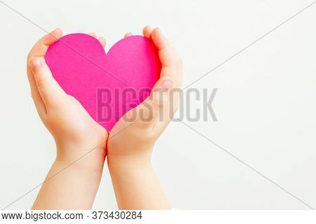 Closeup Of Hands Of Child Holding Paper Pink Heart On White Background. Heart In Hands With Copy Spa