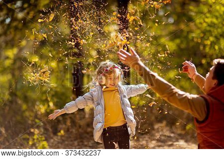 Dad Playing With Daughter, Throw Dry Yellow Fallen Leaves. Walks In An Autumn Park With The Kids.