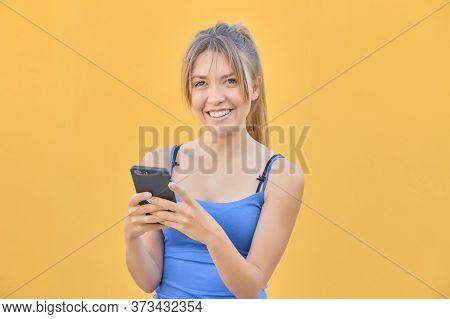 Pretty Blonde Girl Sending A Message Through Her Cell Phone