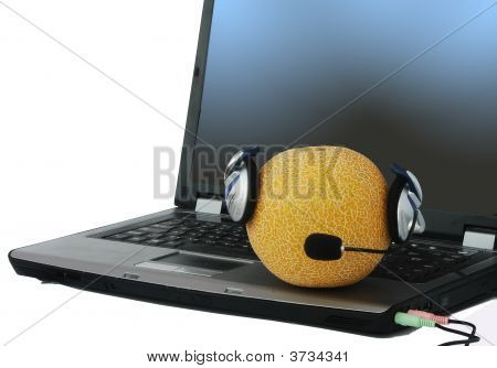 Melon In Headphone Laying On Notebook