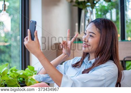 Beautiful And Cute Asian Women Uses The Phone To Take A Selfie. Women Are Happy And Enjoy Taking Pho