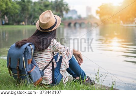 Asian Woman Tourists Backpacker See The Sunset. She Has A Happiness. During Travel. At The Waterfron