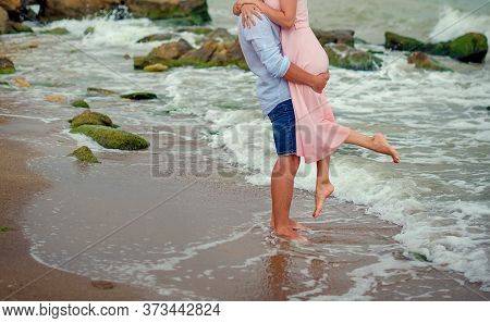 The Guy Holds The Girl In His Arms On The Beach In The Water Barefoot In The Wet Sand. Man And Woman