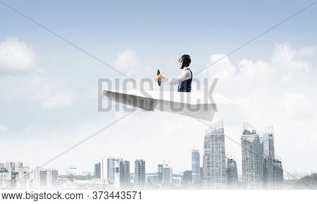 Businessman In Aviator Hat And Goggles Driving Paper Plane Above Downtown With High Buildings. Moder