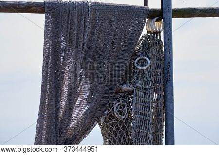 Fishing Nets Hang From A Wooden Beam. Against A Blue Sky. Still Life And Objects. Fishermen, Fishing
