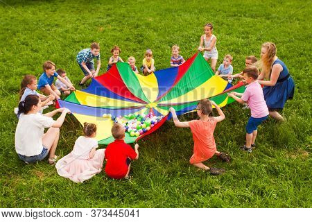 Cheerful Kids Playing With Multicolor Parachute And Small Balls