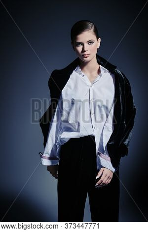 Fashion concept. Portrait of a gorgeous graceful young woman model posing in black velvet suit and white shirt on a gray background. Makeup and cosmetics.