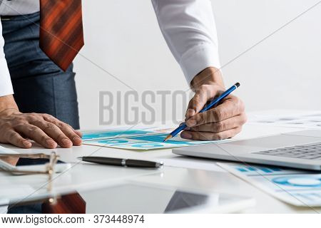 Businessman Standing Near Office Desk With Financial Charts. Ambitious And Determined Man In Busines