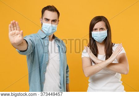 Two People In Sterile Face Masks White T-shirts Isolated On Yellow Background Studio. Epidemic Pande