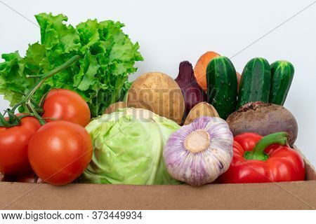 Close-up Fresh Vegetables In A Cardboard Box On A White Background. Fresh And Healthy Food Delivery