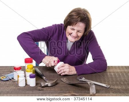 Older women trying to open a medicine bottle