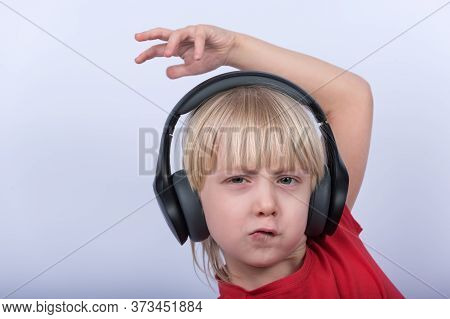Funny Blonde Boy In Big Headphones Listening To Music. Portrait Of Fair-haired Teenager On White Bac