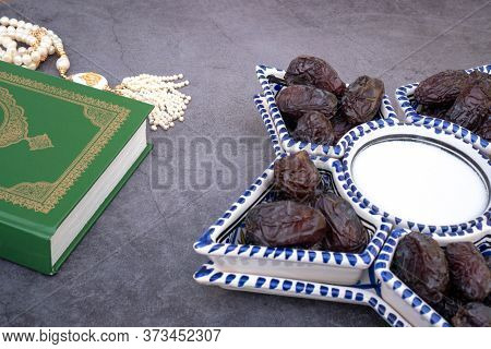 Muslim Islamic Faith Concept Quran Book , White Rosary With The Inscription Allah, Dates In The Bowl