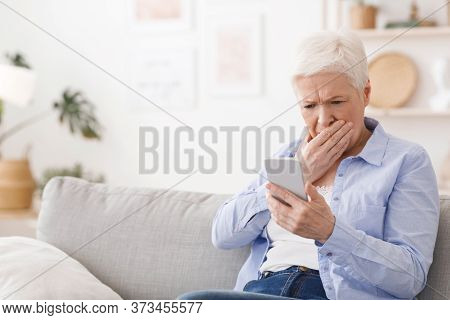 Worried Senior Lady Reading Shocking News On Smartphone At Home, Looking At Screen And Covering Mout