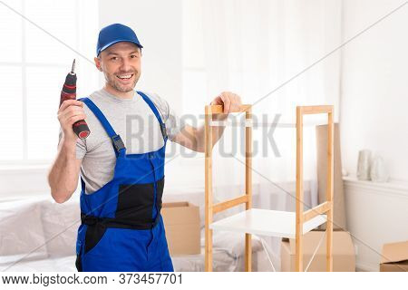 Furniture Assembly. Handyman Worker Posing Installing Cabinet Holding Electric Drill Standing Posing
