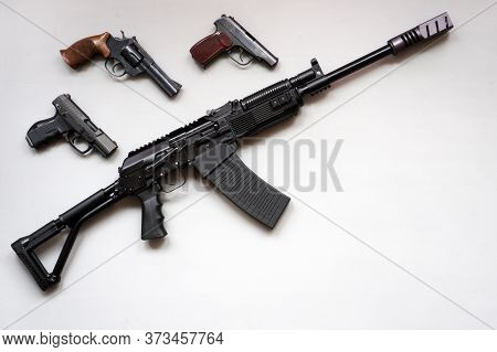 Close-up Of A Boar Machine Gun And Pistols On A Gray Background. Isolated.