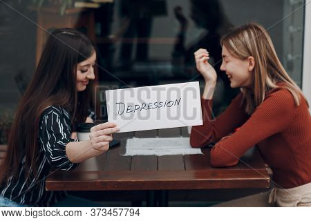 Hidden Depression Concept. Woman Holding White Sheet Paper Labeled Word Depression In Hand. Two Wome