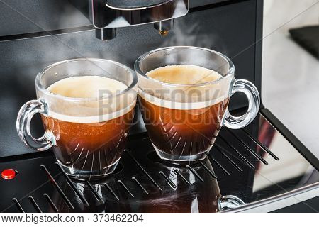 Cups With Hot Coffee Poured From The Coffee Machine