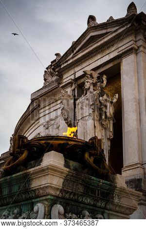 Flame And Statue At The Entrance Of The Monumental Palace Vittorio Emanuele Ii In Rome, Italy