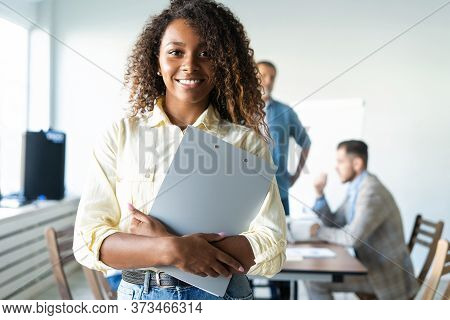Beautiful Young Professional African Woman Standing In Office While Workers Hold A Meeting In Backgr