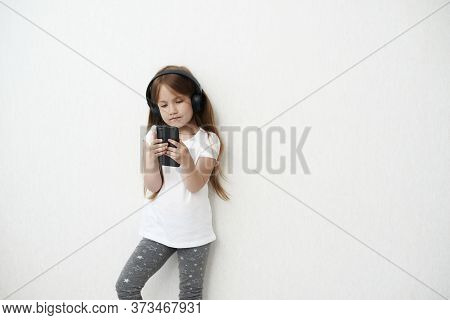 The Little Girl In Headphones. The Girl Is Listening Music. The Little Girl Is Playing Phone On The