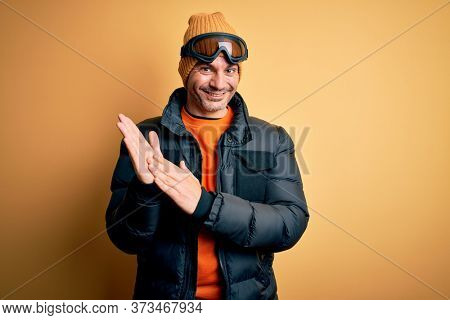 Young handsome skier man skiing wearing snow sportswear using ski goggles clapping and applauding happy and joyful, smiling proud hands together