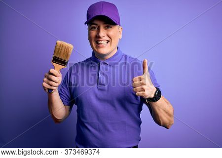 Young modern decorator painter man holding paint brush over purple background happy with big smile doing ok sign, thumb up with fingers, excellent sign