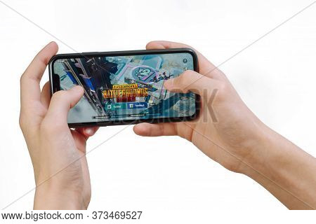 Samara Russia - 04.05.2020: Hands Holding A Smartphone Iphone 11 With Pubg Mobile Game On Display Sc