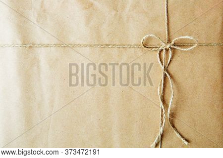 Overhead View Of A Single Holiday Package Wrapped With Eco Friendly Craft Paper And Tied With Twine