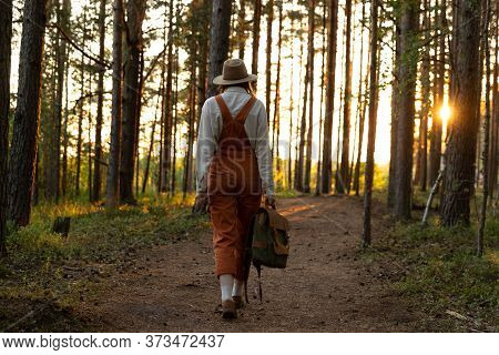 Woman Botanist In Orange Overalls With Backpack On Ecological Hiking Trail In Forest. Naturalist Exp