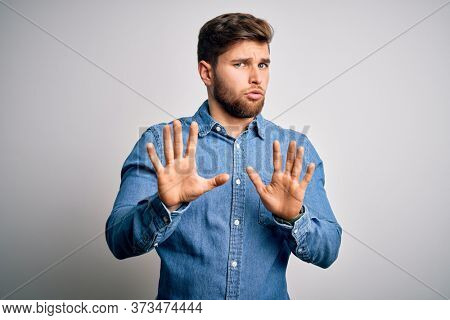 Young handsome blond man with beard and blue eyes wearing casual denim shirt Moving away hands palms showing refusal and denial with afraid and disgusting expression. Stop and forbidden.