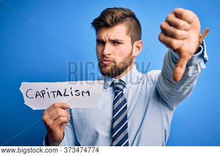 Young blond businessman with beard and blue eyes holding paper with capitalism message with angry face, negative sign showing dislike with thumbs down, rejection concept