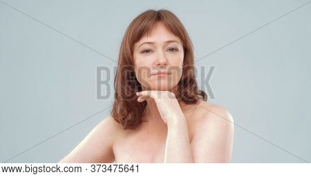 Confident Middle Aged Woman Looks At The Camera With His Hand Near The Chin. Nude Beautiful Caucasia