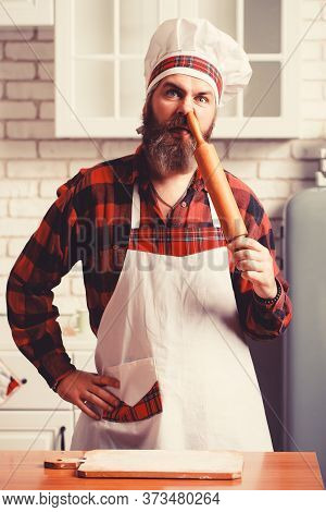 Bearded Chef Sticks A Rolling Pin In His Nose. Crazy Chef In A White Kitchen. Very Funny Photo.