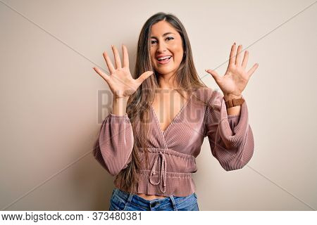 Young beautiful brunette elegant woman with long hair standing over isolated background showing and pointing up with fingers number ten while smiling confident and happy.