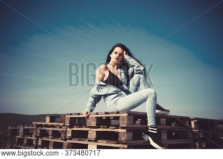 Beautiful Sexy Girl With Long Legs In Jeans Short Overalls Sits On Pallets Setting Her Long Silky Ha