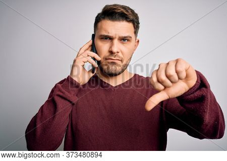 Young man with blue eyes speaking on the phone having a conversation on smartphone with angry face, negative sign showing dislike with thumbs down, rejection concept