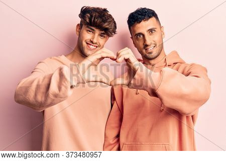 Young gay couple wearing casual clothes smiling in love doing heart symbol shape with hands. romantic concept.