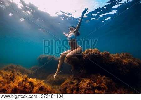 Woman Free Diver With Fins Dive Underwater. Freediving In Blue Ocean