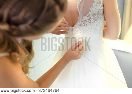 Bridesmaid Helping Slender Bride Lacing Her Wedding White Dress, Buttoning On Delicate Lace Pattern