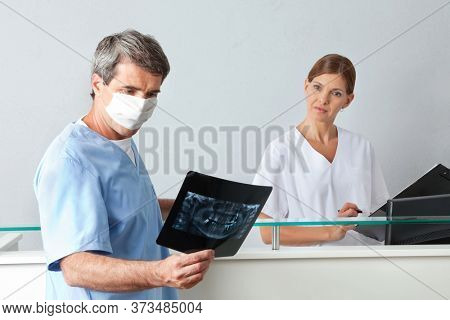 Dentist next to dental assistant looks at x-ray picture of dentition