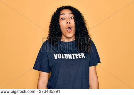 Young african american curly woman doing volunteering wearing volunteer t-shirt scared in shock with a surprise face, afraid and excited with fear expression
