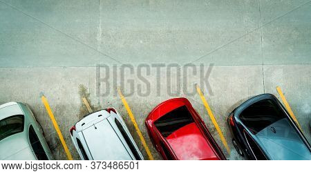 Top View Of Car Parked At Concrete Car Parking Lot With Yellow Line Of Traffic Sign On The Street. A