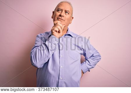 Middle age handsome hoary man wearing casual shirt standing over pink background with hand on chin thinking about question, pensive expression. Smiling with thoughtful face. Doubt concept.