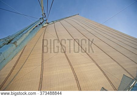 Abstract View Of Wooden Sailing Boat Mast With Rigging On Blue Sky Background