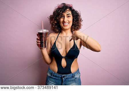 Beautiful arab woman on vacation wearing swimsuit drinking cola refreshment using straw with surprise face pointing finger to himself
