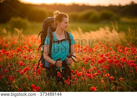 Pretty Woman With Backpack And Walking Sticks Stands On Field Of Poppies And Looks Away